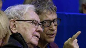 Bill Gates och Warren Buffett trängs på en åskådarbänk på hästhoppstävling. Buffett pekar på något utanför bilden.
