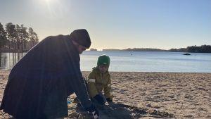 Ted leker på stranden med sin son Lo.