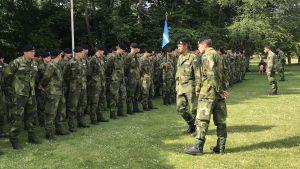 Två militära befäl granska grönklädda soldater uppställda på en gräsmatta.