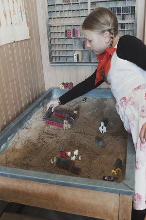 Flicka leker bygger liten by av träklossar i sandlåda.