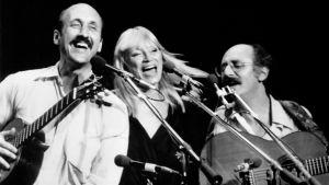 Kaksi miestä ja nainen keskellä soittavat ja laulavat riehakkaan näköisesti.