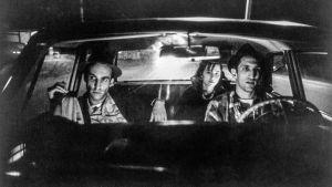 Kolmikko autossa öisellä tiellä. Kuva Jim Jarmuschin elokuvasta Muukalaisten paratiisi.