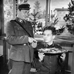 Ylivääpeli (Pentti Viljanen) yllättää ylellisen aterian tilanneen alokkaan (Lasse Pöysti).