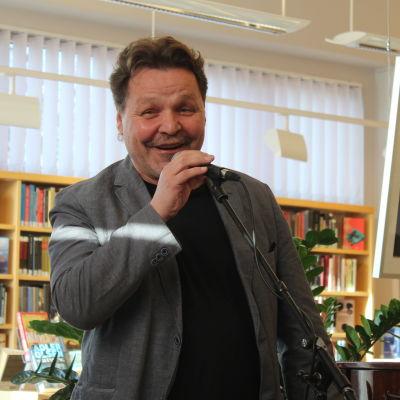 Arto Huhtinen puhuu mikrofoniin kirjastossa