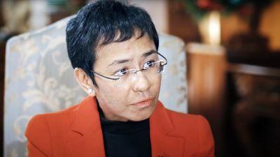 Maria Ressa istuu tuolissa. Hänellä on lyhyet mustat hiukset ja silmälasit. yllään punainen takki ja musta paita.
