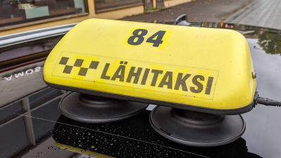 Lähitaksis taxiskylt på ett biltak.
