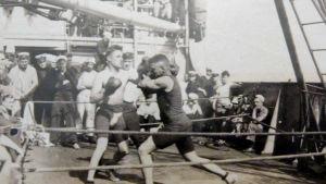 En svartvit bild med en boxningsmatch på ett lastfartyg.