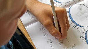 Närbild på en elevs hand som skriver i matematikboken.