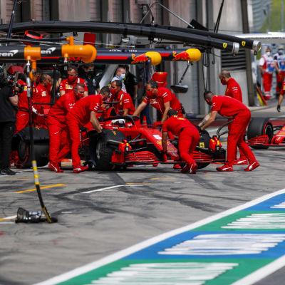 Mekaniker rullar in Ferraribilarna i garaget.