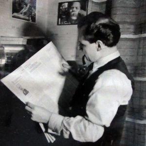 Piippua poltteleva tummahiuksinen mies lukee sanomalehteä