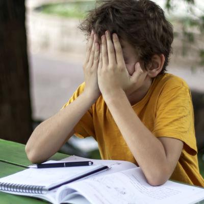 Ett barn sitter vid ett bord med skolböcker framför sig. Barnet håller sitt ansikte i sina händer och ser ledset ut.
