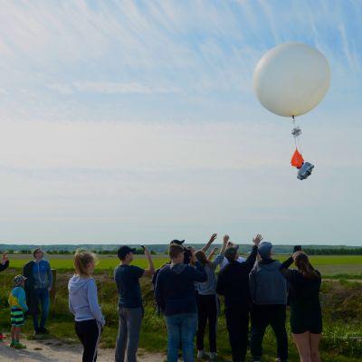 En grupp människor ser på då en väderballong svävar iväg.
