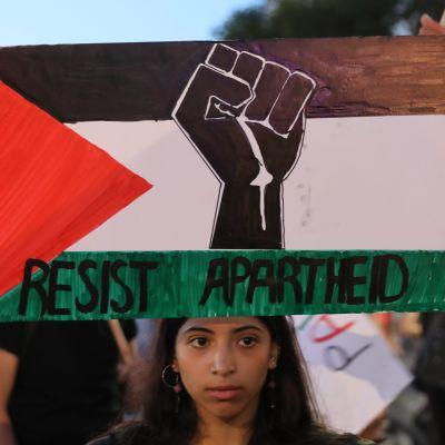 """En aktivist håller upp en palestinsk flagga med texten """"motstå apartheid"""" under en protest i Tel Aviv i fjol somras."""