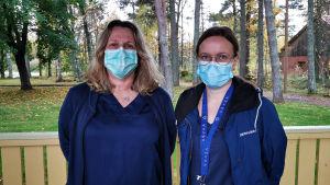 Koronakartoittajat Gun Grangärd ja Sari Kauppinen seisovat katoksen alla hoitajavaatteissaan ja maskit kasvoillaan.
