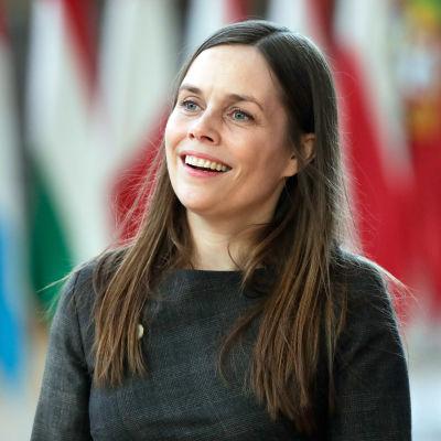 Katrin Jakobsdottir ler och tittar åt sidan. I bakgrunden syns flera flaggor på rad.