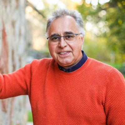 En man i orange tröja lutar mot en stenvägg och tittar in i kameran. Han ler.