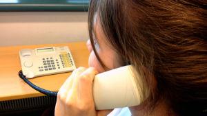 Människa pratar i trådtelefon.