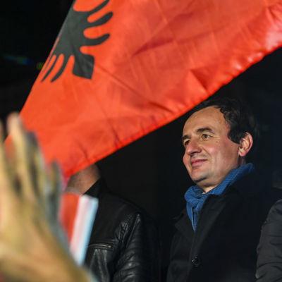 Vetevendosjes partiledare, valsegraren Albin Kurti står bland flaggor och ser ut att vara redo att hålla ett framförande.
