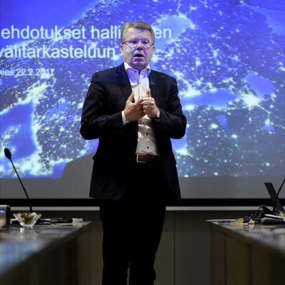 Jyri Häkämies står framför en presentationsprojektion.