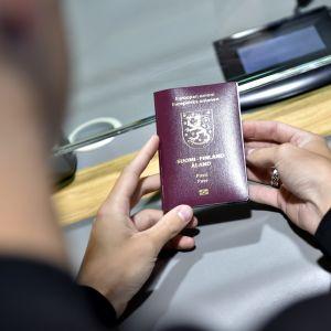En person håller i Finlands pass.