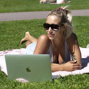 Nainen makaa puistossa tietokoneen ääressä ottamassa aurinkoa.