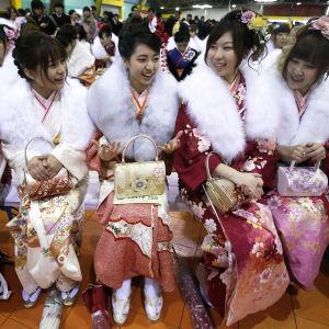 20-vuotiaiden tyttöjen aikuistumisjuhlan osallistujia kimonoissaan ja turkisshaaleissan.