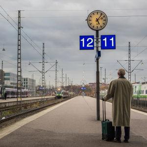Mies odottaa junaa asemalla.