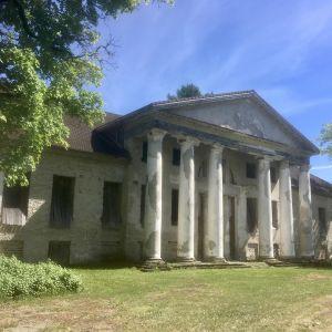 Raikküla gårds historiska corps-de-logi omgiven av full sommargrönska