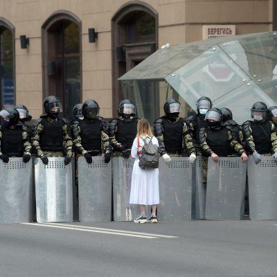 En vitklädd kvinna står framför en rad poliser i full kravallutrustning