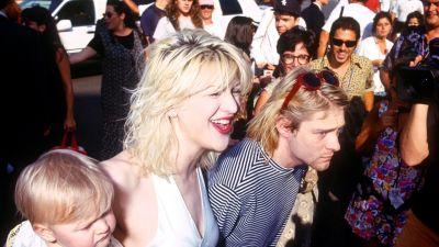 Courtney Love och Kurt Cobain med lilla Frances Bean på MTV Video Music Awards 1993 omgivna av folk.