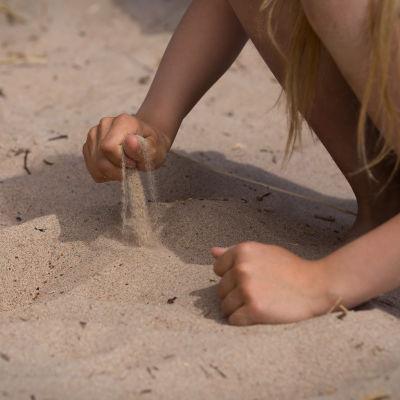 Anonyymi tyttö leikkii hiekalla rannalla kesälomalla aurinkoisella säällä.