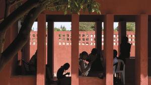 Kvinnor i samvaro i skuggan under soltaket på kvinnocentret i Rufisque i Senegal.