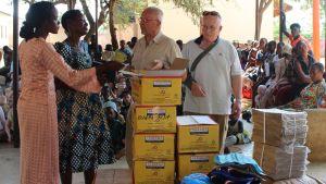 Två (vita) män står vid en stor hög med lådor och andra förpackningar tillsammans med några afrikanska kvinnor. I bakgrunden en massa barn som sitter och följer med. Platsen är i en skola i Tanzania i Afrika.