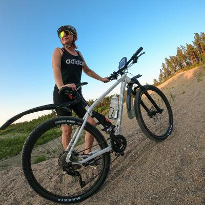 Anneli Magnusson står på en grusväg och håller i en stående terrängcykel. Hon har på sig träningskläder, cykelhjälm och solglasögon