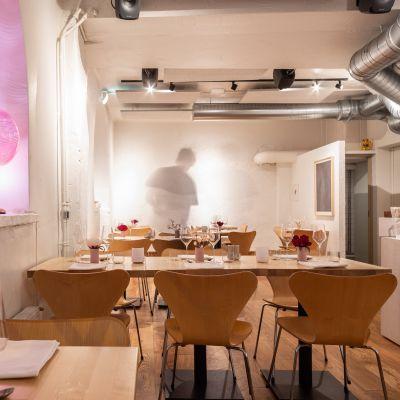 Bild på restaurang med dukade träbord med trästolar intill borden.