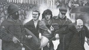 En man framför en politisk väggmålning i Derry.