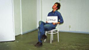 Mecki Andersson istuu tuolilla tyhjässä huoneessa vuonna 1986, sylissään kyltti: After Eight
