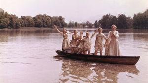 Maria (Julie Andrews) och alla von Trapp-barnen står upp i en roddbåt.