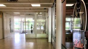 En sliten interiör, ett tomt väntrum på busstationen i Karis. Gulbrunt golv, vita väggar. Utanför skiner solen.
