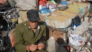 Medelålders man rullar cigarett och säljer tobak på torg i Kina.