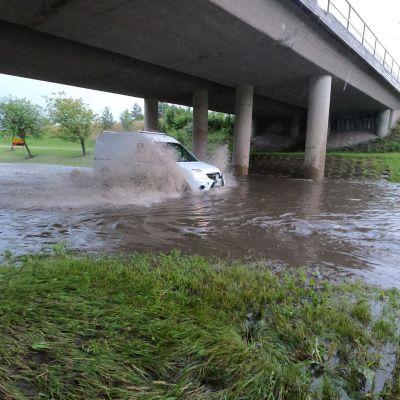 auto ajaa tulvivasta alikulku tunnelista