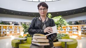 Minna Koistinen, en dam med glasögon och svart läderjacka, håller i en hög med böcker i ett bibliotek.