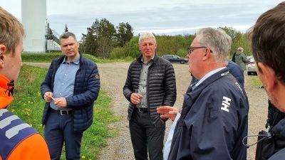 En grupp män diskuterar hur den estniska utbildningen av vindkraftverkstekniker kan arrangeras utomhus på ett lobbningsevenemang.