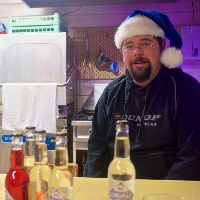 En man med blå tomteluva sitter bakom disken i en kiosk.