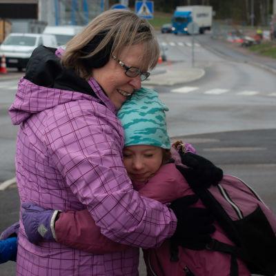 Seija Vahvelainen halaa lapsenlastaan ulkona tämän lähtiessä kouluun.