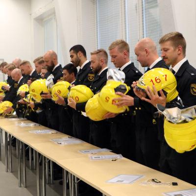 Brandmännen lägger på sina hjälmar.