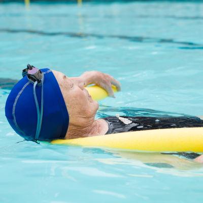 En kvinna ligger på rygg i en bassäng och flyter med hjälp av ett flytetyg.