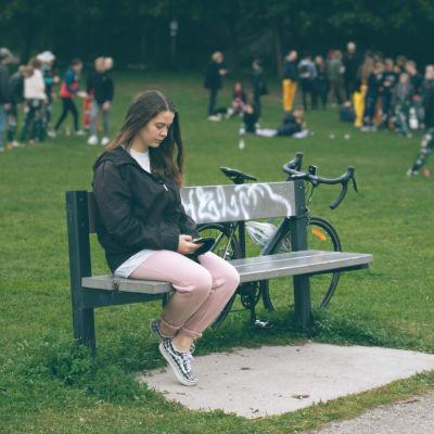 Nuori nainen istuu yksin puistonpenkillä älypuhelin kädessään. Taustalla muut nuoret pitävät hauskaa