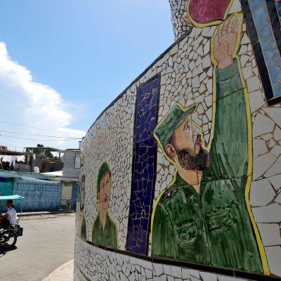 Sotilaspukuinen mies nostaa kättä seinämaalauksessa, polkupyöräriksa kulkee ohi