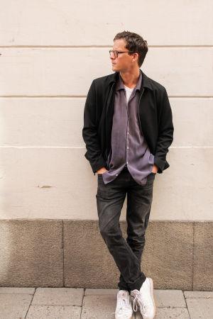 På bilden syns skådespelaren Adam Pålsson i helprofil. Han står lutad mot en ljus fasadvägg och hans huvud är vänt åt vänster. Han är iklädd mörka byxor och jacka, vita sneakers och glasögon.